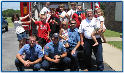 Firefighters and kids at the back of a fire engine posing for a picture